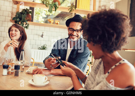 Portrait of young friends talking in cafe and looking at the photos on smart phone. Happy young people having a - Stock Photo