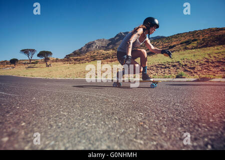 Side portrait of young woman wearing protective gear longboarding outdoors on a road. - Stock Photo