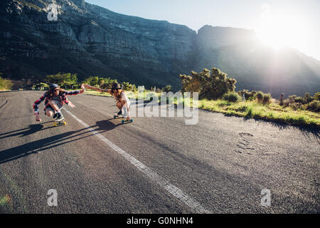 Young couple skating down on the road. Young man and woman having fun while skating together on a sunny day. - Stock Photo