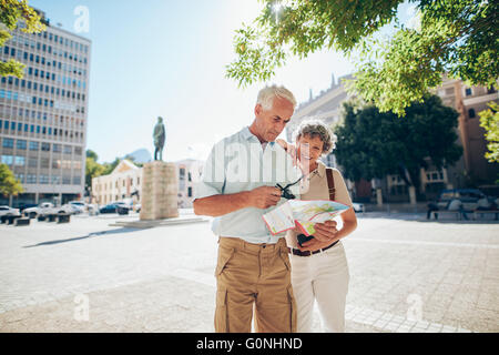 Senior couple using a city map for location in the town. Mature man and woman standing together outdoors in city - Stock Photo