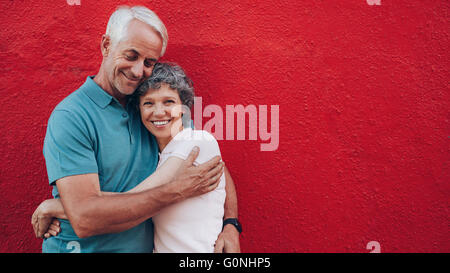 Portrait of affectionate mature couple embracing each other against red background and smiling. Senior couple against - Stock Photo