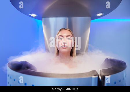 Portrait of a beautiful young woman in cryosauna cabin for whole body cryotherapy. Caucasian female in freezing - Stock Photo