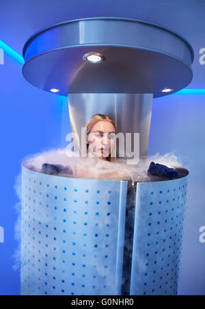 Portrait of beautiful young woman in a full body cryotherapy camber at cosmetology clinic. She is undergoing skin - Stock Photo