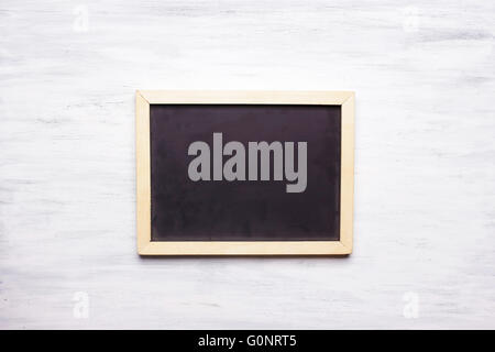 Top view of empty chalkboard with copyspace on white wooden table. - Stock Photo