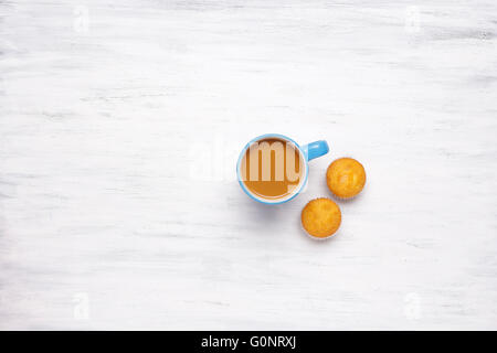 Top view of cup of coffee and muffins on a white wooden table. Break from work, lifestyle concept. - Stock Photo