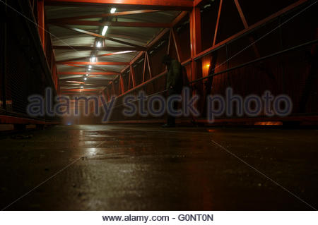Homeless man standing on footbridge path at night in fog - Stock Photo