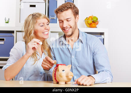 Happy couple putting Euro mony coins in a piggy bank - Stock Photo