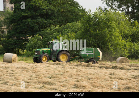 Silage or hay making - man is driving green farm tractor pulling a round baler, working in a field - Great Ouseburn, - Stock Photo