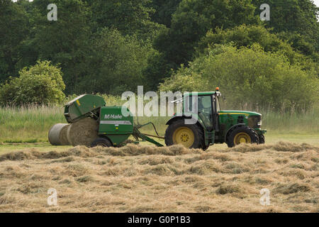 Great Ouseburn, North Yorkshire, GB, UK - round bale dropping & falling from a baler pulled by a green farm tractor - Stock Photo