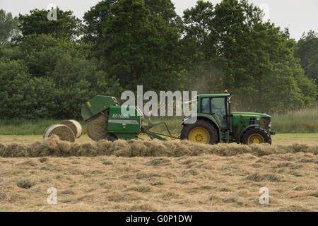 Great Ouseburn, North Yorkshire, GB - cylindrical bale is falling from round baler pulled by farm tractor driving - Stock Photo
