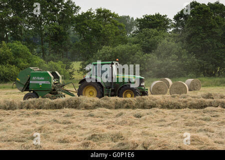 Green farm tractor working in a field, silage or hay making, pulling round baler (4 cylindrical bales beyond) - - Stock Photo