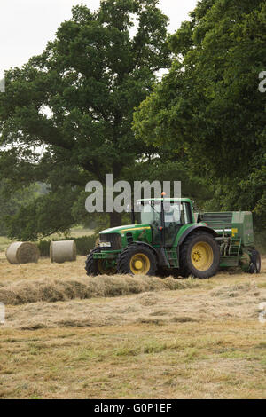 Hay or silage making, Great Ouseburn, North Yorkshire, England, UK - green farm tractor working in a field, pulling - Stock Photo