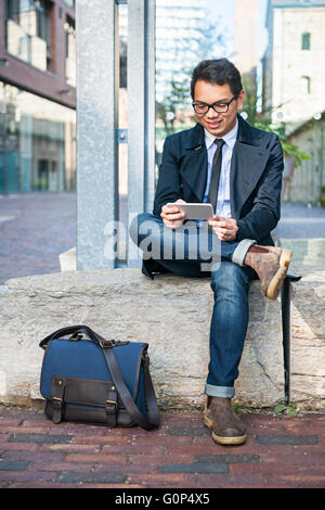 Young smiling asian business man looking at mobile phone sitting outside on city street - Stock Photo