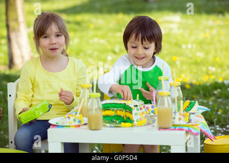 Happy sweet preschool children, friends and relatives, celebrating fifth birthday of cute boy, outdoor in blooming - Stock Photo