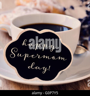 the sentence happy supermom day written in a blackboard in the shape of a thought bubble placed in a cup of coffee, - Stock Photo