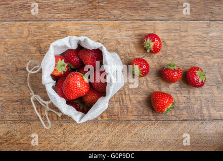 Overhead view of fresh strawberries in a small hessian bag on a wooden kitchen table with a loose strawberries beside - Stock Photo