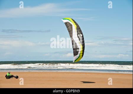 man riding a beach buggy at speed with a power kite on saltburn beach using wind energy on sand by the sea - Stock Photo
