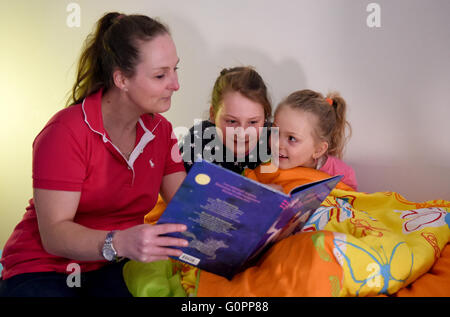 Sisters Skady-Lee (10) and Lucy-Mae (6) sit on a bed next to their mother Wiebke Ruedig at the night nursery at - Stock Photo