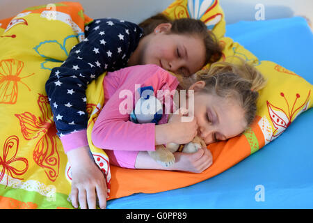 Sisters Skady-Lee (10) and Lucy-Mae (6) lie in a bed at the night nursery at the Kapernaum daycare center, the service - Stock Photo