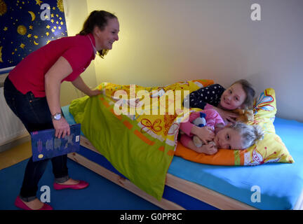 Sisters Skady-Lee (10) and Lucy-Mae (6) are tucked into bed their mother Wiebke Ruedig at the night nursery at the - Stock Photo