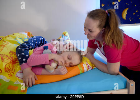 Sisters Skady-Lee (10) and Lucy-Mae (6) lie on a bed next to their mother Wiebke Ruedig at the night nursery at - Stock Photo