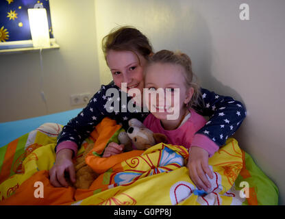 Sisters Skady-Lee (10) and Lucy-Mae (6) sit in a bed at the night nursery at the Kapernaum daycare center, the service - Stock Photo