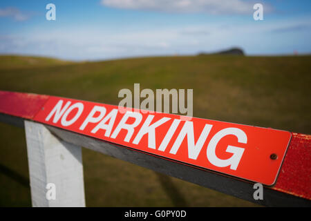 A red no parking sign on a wooden fence. - Stock Photo