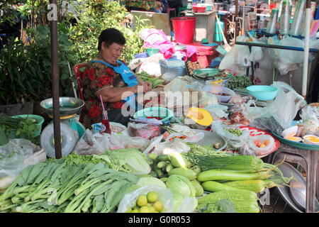 Fresh fruit and vegetable stall in Bangkok. The women sorting the chilies while waiting for customers. - Stock Photo