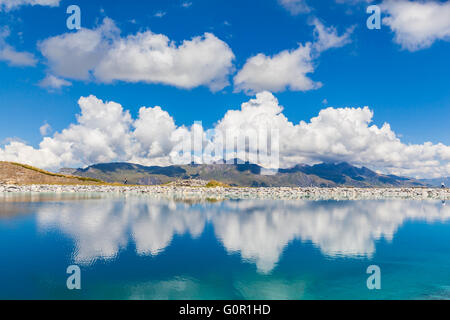 Stunning view of the Fallbodensee (lake) on Bernese Oberland with reflection of clouds and mountain ranges, Switzerland. - Stock Photo