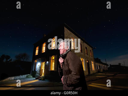 Grumpy old man in a street on a cold winter night - Stock Photo