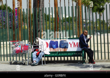 Homeless mentally ill man and man on cell phone at bus stop in Los Angeles Southern California United States of - Stock Photo