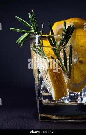 gin with tonic, lemon and rosemary on  dark background - Stock Photo