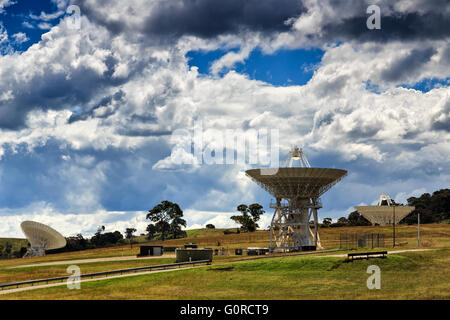 An array of satellite radio antenna dishes searching the signal and communicating with satellites from green hill - Stock Photo