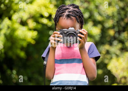 A child is taking picture with camera - Stock Photo