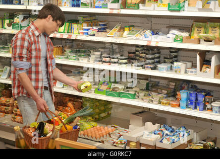 Man in organic grocery store, health food store, wholefood shop, customer, cooling shelf, dairy goods, self-service, - Stock Photo