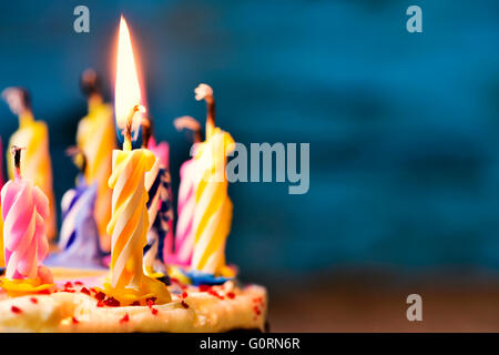 closeup of some unlit candles and just one lit candle after blowing out the cake - Stock Photo