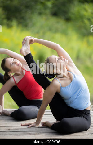 Yoga class: Two serene young beautiful women working out outdoors in park on summer day, sitting in Parivrtta Surya - Stock Photo
