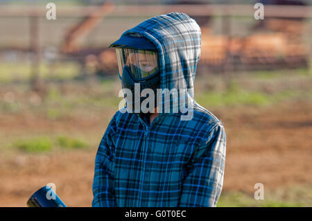 Boy in mask and hooded jacket playing paint ball outdoors. - Stock Photo