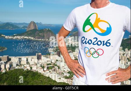 RIO DE JANEIRO - MARCH 21, 2016: Man stands in souvenir Rio 2016 shirt under bright blue sky above the city skyline. - Stock Photo