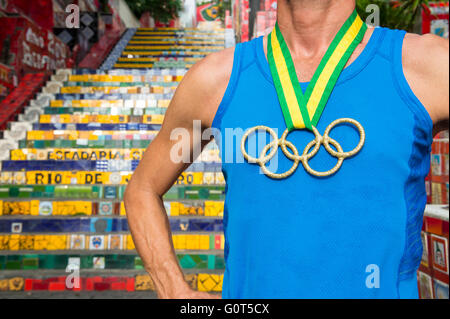 RIO DE JANEIRO - MARCH 29, 2016: Athlete with gold medal Olympic Rings stands outdoors in front of the famous Selaron - Stock Photo