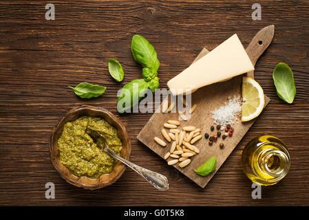Fresh basil pesto with ingredients on wooden background. - Stock Photo
