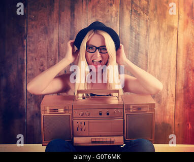A blonde hipster girl with glasses is listening to a vintage gold boombox radio with a speaker for a music entertainment concept