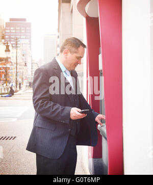 A business man is holding a phone and withdrawing money from his account at an automatic teller machine downtown - Stock Photo