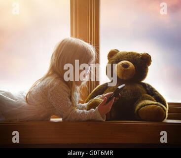 A little child is playing with an electronic tablet in a window with her teddy bear for a game, app or entertainment - Stock Photo