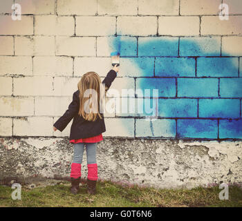 A little child is painting an old white brick wall with blue paint for creative art concept or design idea. - Stock Photo