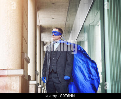 A super business man is wearing a blue cape confident in the city for a success, entrepreneur or inspiration concept. - Stock Photo