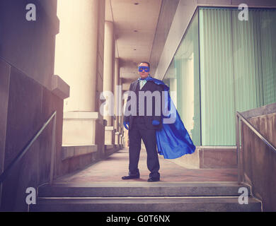 A business man is wearing a super hero blue costume with a suit in a city for a career success or innovation concept. - Stock Photo