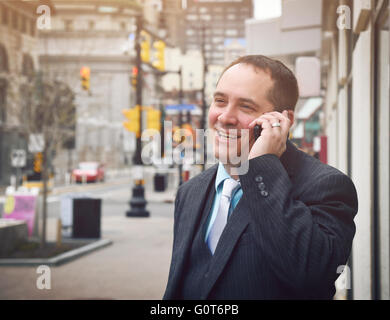 A business man is talking on a cell phone outside in a city wearing a suit and smiling for a success or communication - Stock Photo