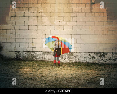 A little child is standing against a brick wall holding a rainbow umbrella outside for a hope, peace or creative - Stock Photo