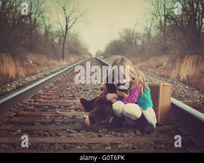 A little girl is sitting on an old train track outside and hugging a teddy bear for a vintage memory or travel concept. - Stock Photo